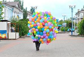 mannen bär många ljusa ballonger foto