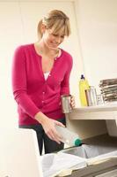 kvinna som återvinner avfall hemma foto