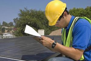 underhållsarbetare som gör anteckningar nära solpaneler