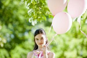 liten flicka med rosa balllons foto