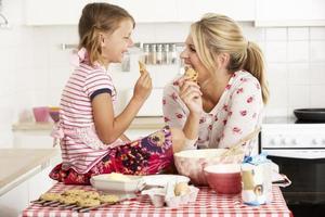 mor och dotter bakning i köket foto