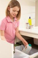 ung flicka som återvinner avfall hemma foto