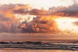 fluffiga solnedgång moln över vågorna