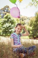 söt liten flicka som håller ballonger