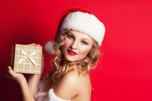 vacker ung kvinna som bär jultomten kostym innehav gåva b foto