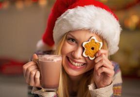 flicka i santa hatt med kaka och kopp choklad foto