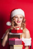 vacker ung kvinna som bär jultomten kostym innehav colorf foto
