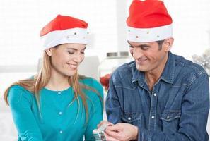 lyckligt leende par som kopplar av med julklappar hemma
