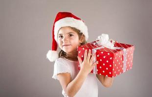 liten flicka i santa hatt med julklapp foto