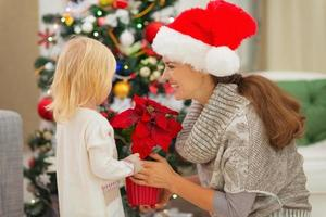 mamma och baby flicka nära julgran foto