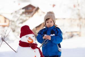 lyckligt vackert barn som bygger snögubbe i trädgården, vinter foto