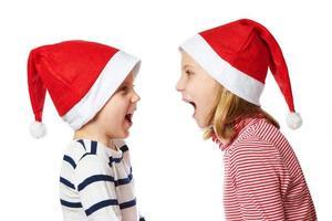 flicka och liten pojke i jultomtenhatt foto