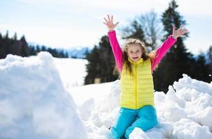 glad liten flicka har kul med snö utomhus foto