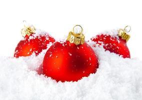julferiedekoration med vit snö och röda bollar foto