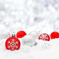 julgranskulor i snö med silverbakgrund foto