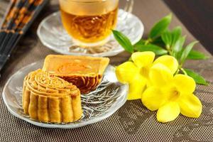 utsökt mooncake och varmt te med gula blommelement. foto