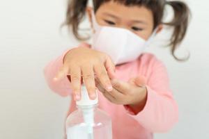 liten flicka som använder handdesinfektionsmedel