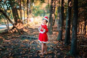 asiatisk tjej i röd jultomtendräkt med nuvarande låda