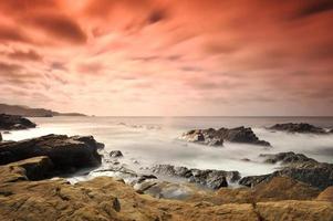 svart klippformation på havsstranden under dagtid