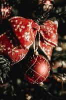 en röd och guld rosett som hänger på ett julgran