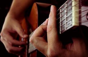man spelar akustisk gitarr foto