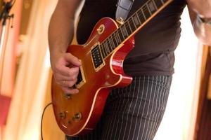 musiker spelar på gitarr foto