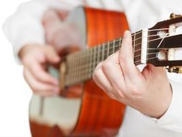 man som spelar klassisk gitarr på nära håll isolerat