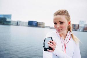 fit ung dam övervaka hennes framsteg på smartphone foto