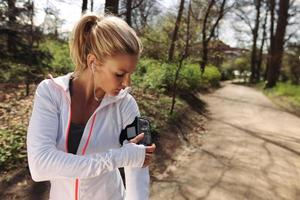 kvinnlig löpare övervaka hennes framsteg på smartphone foto