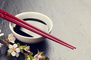 japanska sushi ätpinnar, sojasåsskål och sakura blomning foto