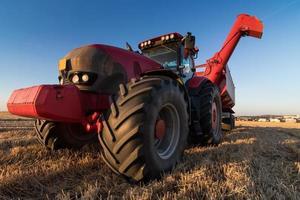 jordbrukstraktor på stubbfält foto