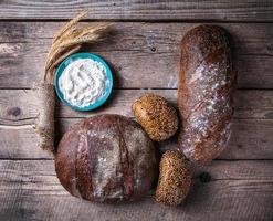 rustika bröd, vete och mjöl på träbakgrund foto