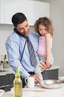 välklädd far med dotter som förbereder mat medan han är på samtal foto