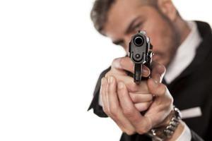 man i kostym och pistol foto