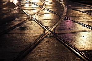 våta vagnskenor på gatorna reflekterar ljus