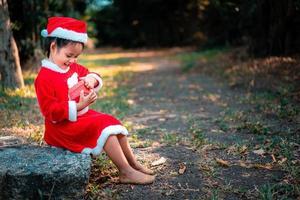 liten asiatisk tjej i röd jultomtendräkt med nuvarande låda