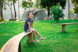 liten flicka som sitter på bänken