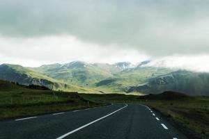 väg mot bergbakgrund, island, molnigt sommarväder