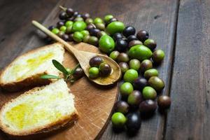 olivolja och bröd på rustikt träbord foto