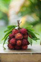 rambutan frukter och blad i en massa på bordet
