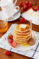 pannkakor med jordgubbar, smör och honungsirap