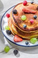 amerikanska pannkakor med färsk frukt till frukost foto