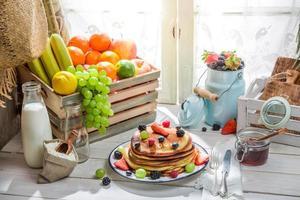friska pannkakor med frukt och lönnsirap foto