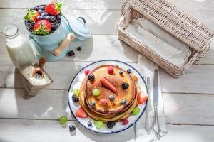 amerikanska pannkakor med lönnsirap och frukter foto