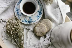 kopp kaffe och kex på bricka