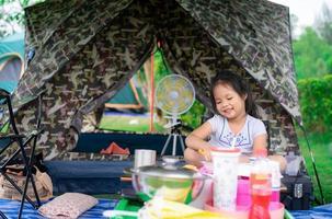 liten flicka som sitter framför tältet