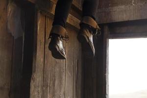 person som dinglar fötterna i en ladugård