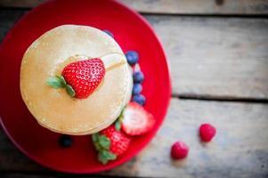 hemlagade pannkakor med jordgubbar, blåbär och lönnsirap på bakgrund foto