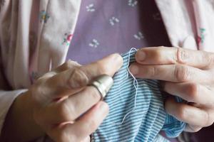 hemming en klänning, kvinnan räcker handarbete foto
