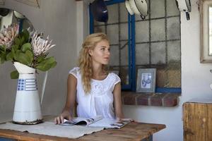 flicka sitter på ett bord läsa tidningen foto